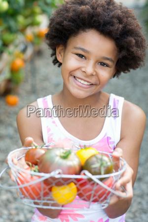 girl holding basket of ripe tomatoes
