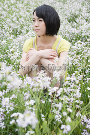 young woman sitting in field of