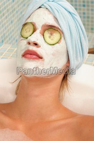 young woman having facial in bath