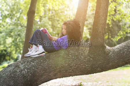 young girl lying on tree branch