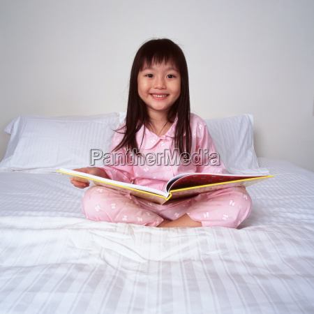 young girl on bed with book