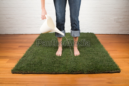 a woman watering grass