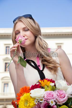 giovane donna che profuma rosa dal