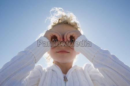 girl looking through hands