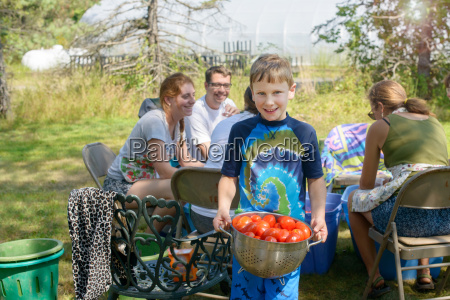 family with young boy holding colander