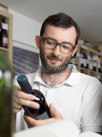 bearded and bespectacled man holding wine