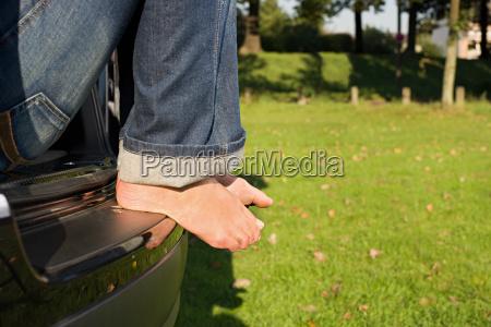 feet of man sitting on car