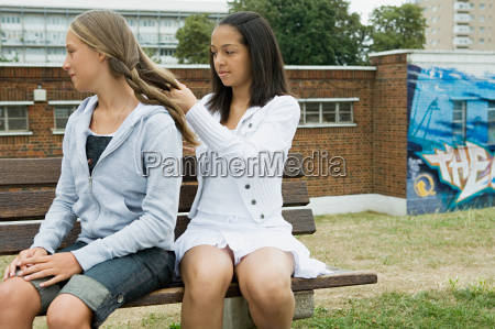 girl playing plaiting friends hair