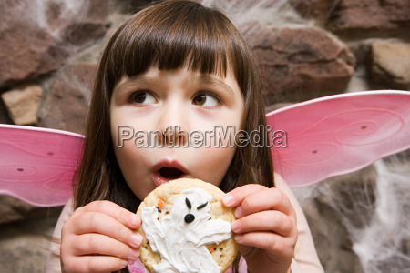 girl holding a halloween cookie