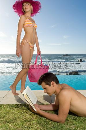 man reading as woman walks by
