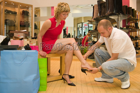 man helping girlfriend try on shoes