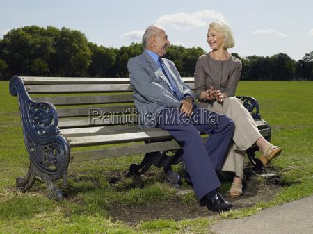 elderly couple sitting on a park