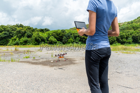 woman control flying drone