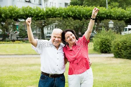 portrait of elder couple raising their