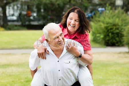 senior man piggybacking his wife