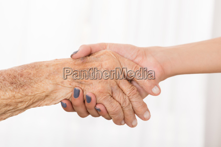 senior patient shaking hand with female
