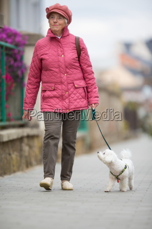 senior woman walking her little dog