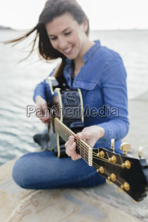 smiling young woman sitting on dock