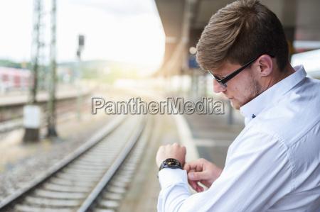 young man at station platform checking
