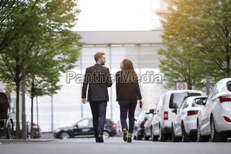 businessman and businesswoman walking outdoors