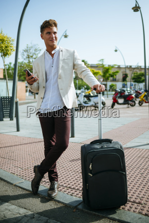 young man with suitcase and cell