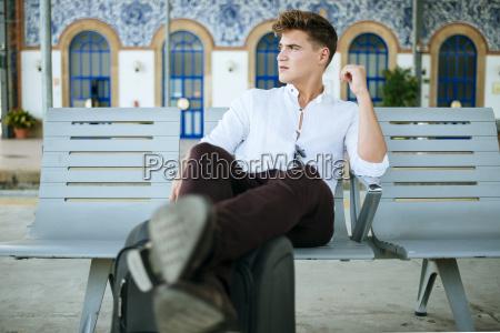 young man waiting at station platform