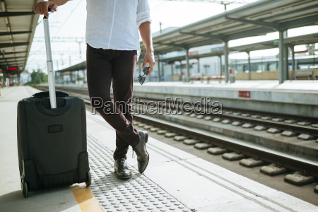 man with suitcase waiting at station