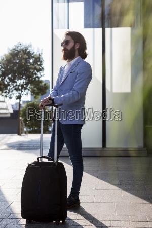 stylish businessman walking with suitcase outdoors