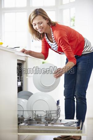 donna caricamento piastre in lavastoviglie