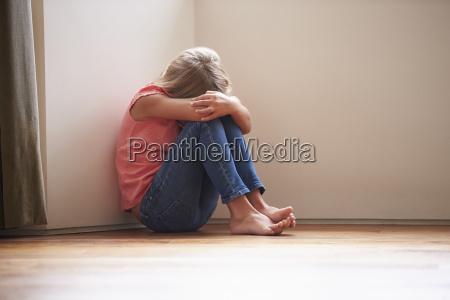 bambino infelice seduto sul pavimento in