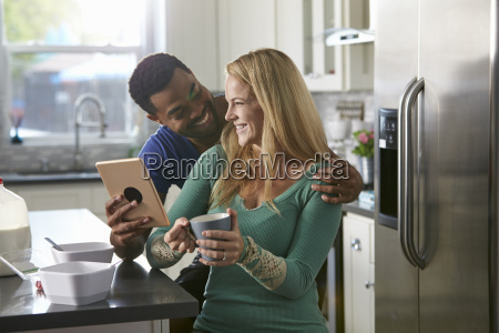 mixed race couple using a tablet