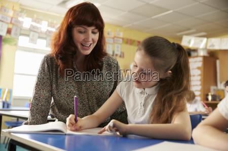 insegnante della scuola primaria aiutando con