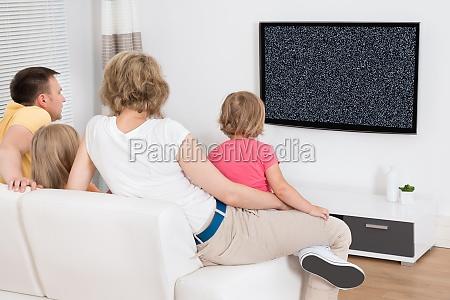 giovane famiglia che guarda insieme tv
