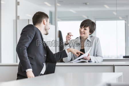 businesspeople standing doing paperwork in office