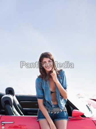 woman leaning at car smiling