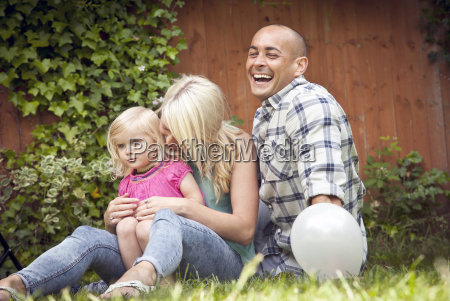 happy couple sitting with toddler daughter
