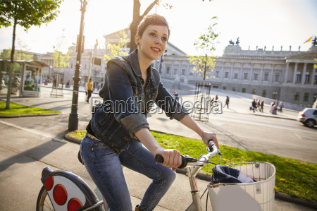young adult woman cycling through city