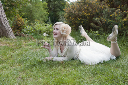 woman lying on grass holding dandelion