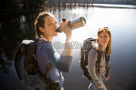 two women sharing water beside lake