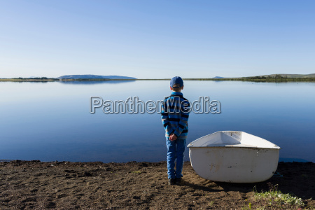 young boy standing next to rowing