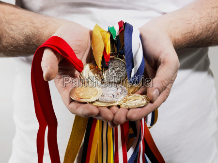 mature man holding gold medals against