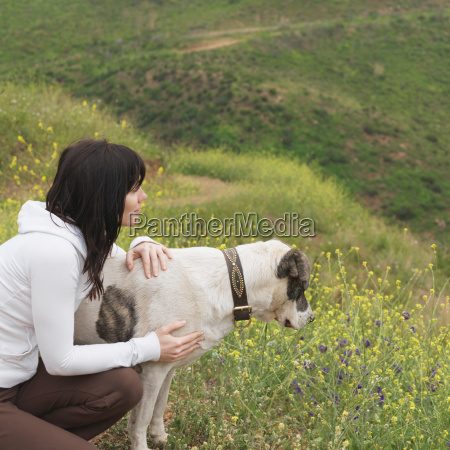 woman hugging dog on nature trail