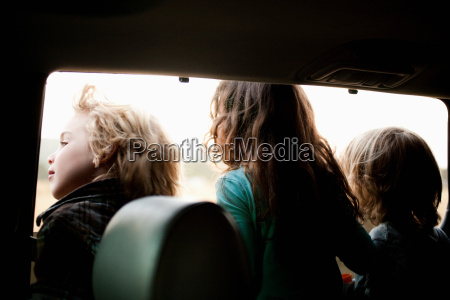 three children looking through car window