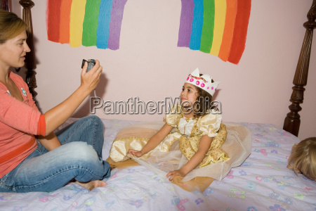 mother photographing daughter dressed up in