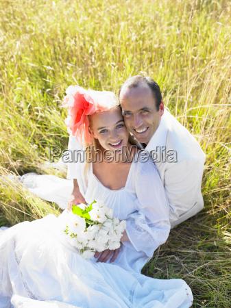 coppia sposata seduta in un campo