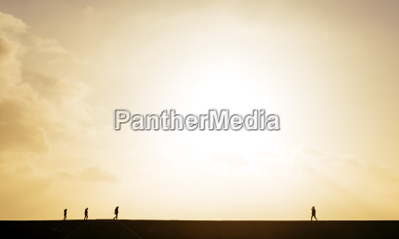 silhouetted view of people strolling on