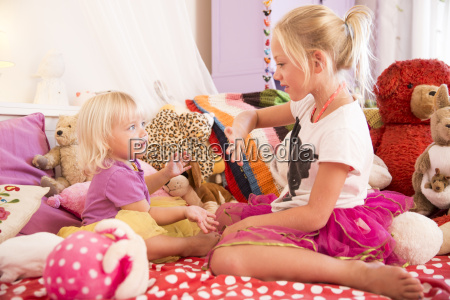 girl and toddler sister playing hands