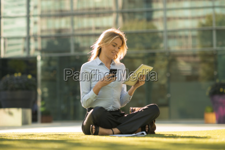 young city businesswoman sitting outside office