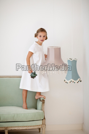 girl with flowers standing on couch