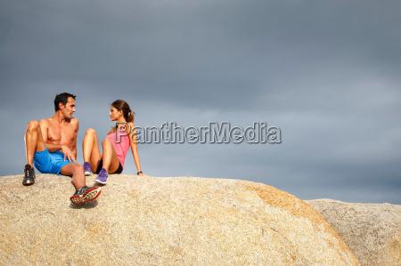 couple sitting on boulder